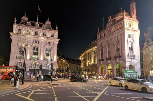 Image of regency style buildings in city lit up at night with black cab and red London bus driving past