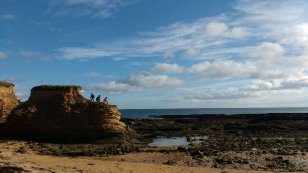 Image of three children on grassy topped sea stack to left of rocky beach with sea and blue sky & clouds behind
