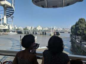 Image of two girls from behind looking out of window onto river with bridge and buildings in background
