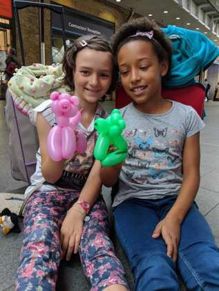 Image of two girls holding balloon animals sat on floor leaning on suitcases with buildings behind