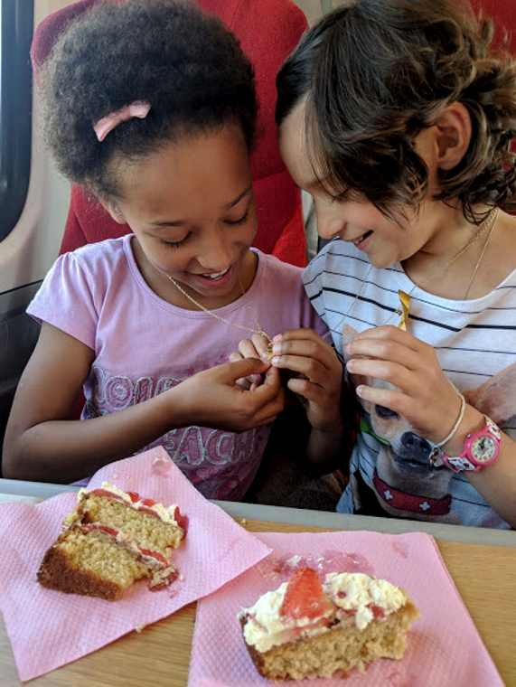 Image of two smiling girls sitting in train seat comparing necklaces with cream cake slices on the table