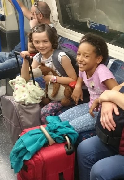 Image of two smiling girls sitting on tube train with suitcases in front of them