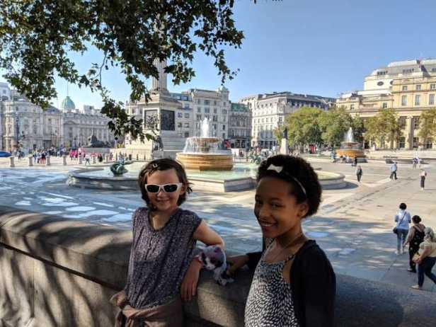Image of two young girls leaning on wall in shade of tree overlooking Trafalgar Square in background