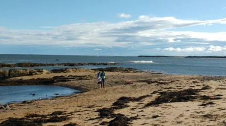 Image of wide sandy beach with two people walking towards camera, rocks in background and wide expanse of sea behind with blue sky
