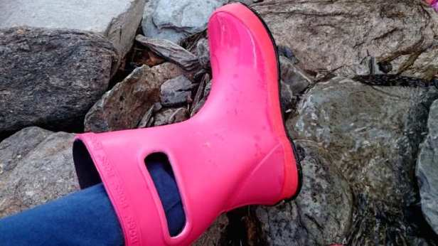 Image close up of matt pink child's waterproof boot with BOGS written around boot top