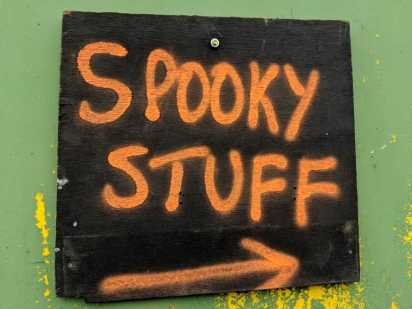 Image of blackboard sign with orange writing stating Spooky Stuff and arrow pointing right