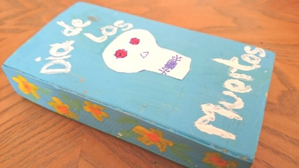 Image of blue hand painted matchbox with white skull and the words Dia de Los Muertos painted on