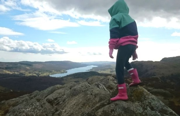 Image of child in pink boot, dark leggings and greena nd red top standing back to camera on top of mountain with far reaching view over hills and lake behind