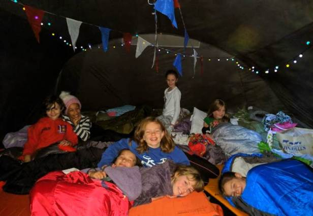 Image of children in camping tent with bunting and fairy lights