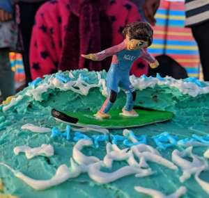 Image of clay figurine model cake decoration of girl in pink and blue wetsuit surfing on blue and white icing sugar waves