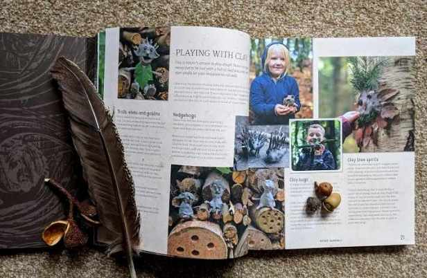 Image of double page spread of book showing children in woodland, with acorn and feather lying on page