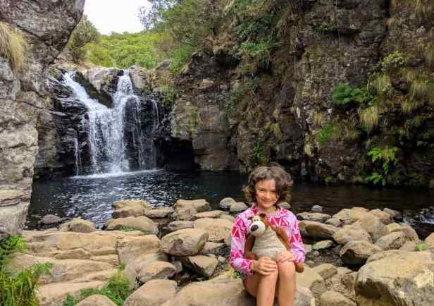 Image of girl holding teddy bear sitting on rocks in front of waterfall pool with rocky cliffs around