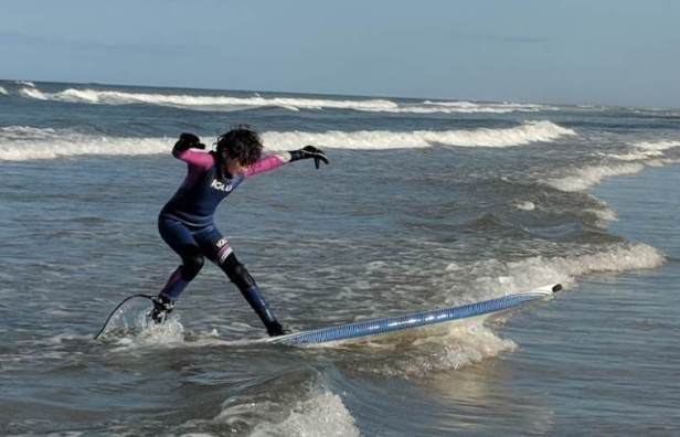 Image of girl in blue and pink Iglu wetsuit surfing a shallow wave in the sea