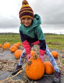 Image of girl in coloured clothes and hat standing over giant pumpkin growing in field of pumpkins