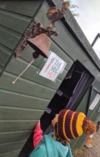 Image of girl in red and yellow harry potter hat looking up at cockerel doorbell on shed with sign stating The Veg Hut