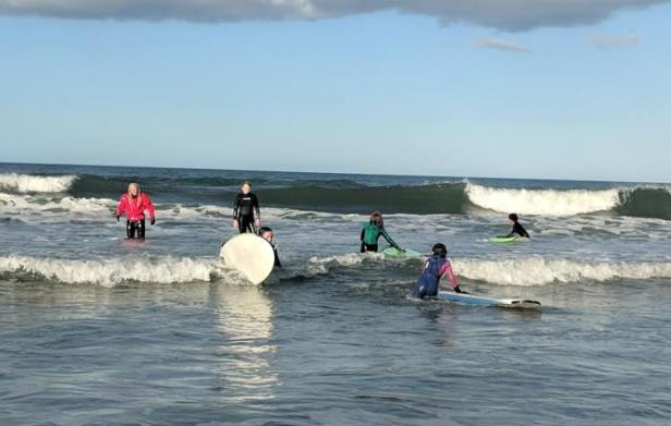 Image of group of children having a birthday party surf lesson in the sea