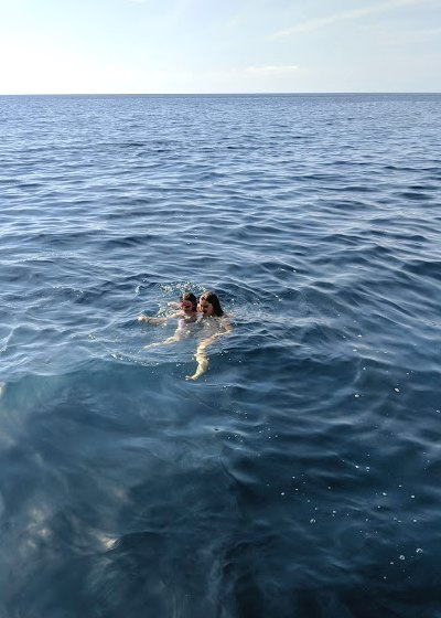 Image of heads of two people bobbing above water in wide expanse of open sea