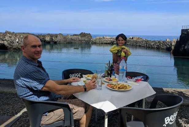 Image of man sat at cafe table with girl stood holding yellow towel and outdoor natural sea pool in background with rock walls and sea behind
