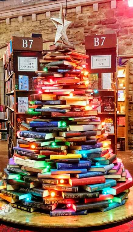 Image of pile of colourful books stacked on table in shape of a Christmas Tree decorated with Christmas fairy lights and star on top of tree