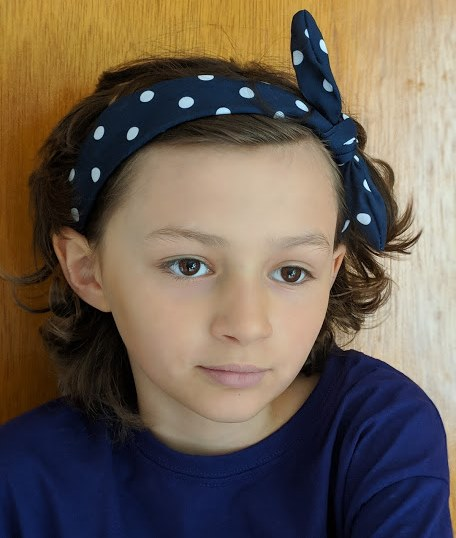 Image of portrait of girl with navy top and hairband