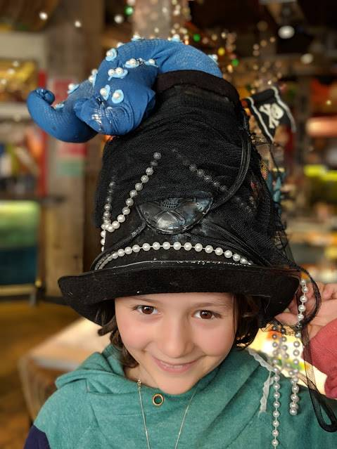 Image of smiling girl in black top hat with blue octopus legs coming out of top