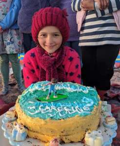 Image of smiling girl in red top and woolly hat with birthday cake in front