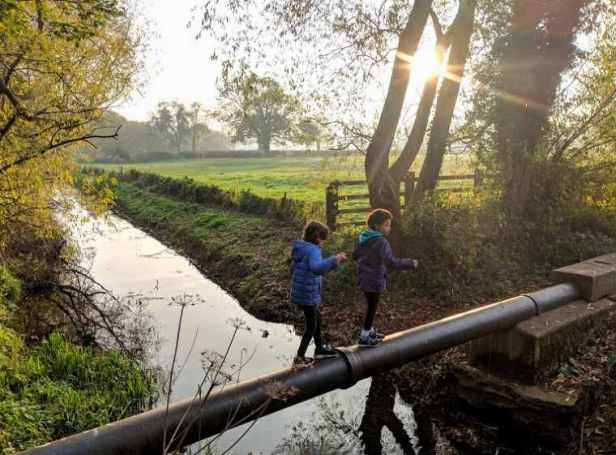 Image of two girls balancing on pipe over river with autumn sun streaming through trees behind