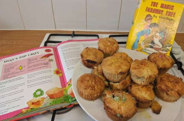 Image of plate of cakes in front of yellow Enid Blyton's Magic Faraway book with book open to left showing recipe for Silky's Pop Cakes