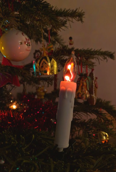 Image single white plastic candle fairy light on evergreen Christmas tree