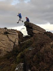 Image of girl jumping across gap between two rocks high in hills