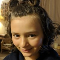 Image of smiling child's face with curly dark hair in pony tail on top of head