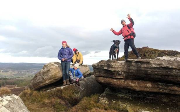 Image of three children, a man and a dog standing on craggy outcrop on top of hill ridge with distant views behind