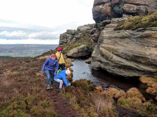 Image of three children playing near hillside pool at bottom of rocky crag with distant views behind