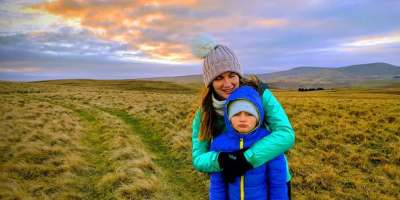 Image of woman and girl in outdoor clothes on top of grassy hill with sunset sky behind