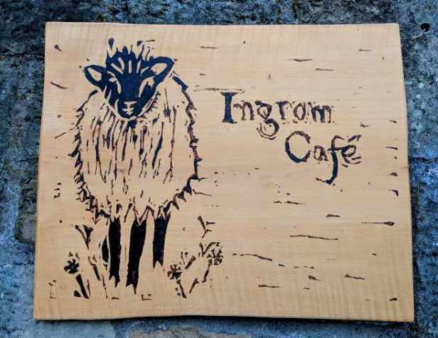 Image of wooden sign with black etching of sheep and words Ingram Cafe