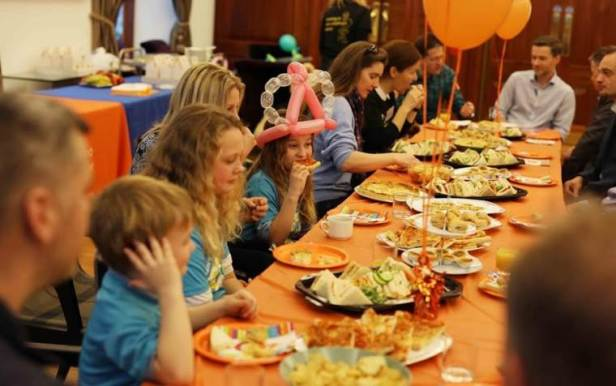 Image of adults and children sat eating party food at buffet table with orange tablecloth and balloons