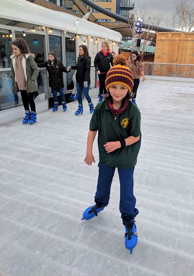 Image of gilr in dark green T-shirt on open air ice rink