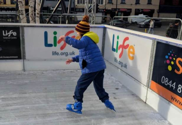 Image of girl in blue jacket and striped woolly hat ice skating at Science Life Centre, Times Square, Newcastle