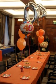 Image of long buffet table with orange tablecloth and silver 40th balloons