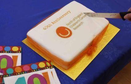 Image of white iced rectangular cake with orange writing 40TH ANNIVERSARY NORTH OF ENGLAND CHILDREN'S CANCER RESEARCH