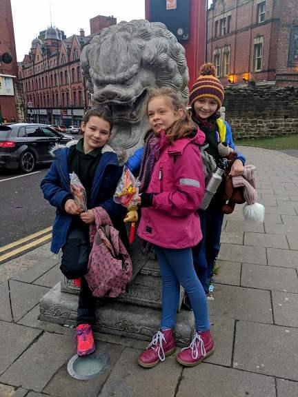 Three girls stood next to stone Chinese dragon at Chinatown gate, Newcastle, UK