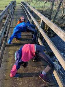 Image of 3 girls doing acrobatic backbends on wooden footbridge over a river while wearing boots with felted feet underneath
