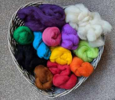 Image of brightly coloured rolls of sheeps wool roving for felting in a heart shaped basket