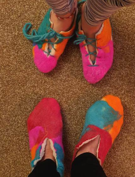Image of two pairs of feet stood toe to toe from above wearing brightly coloured felt slippers, one with wool laces tied in a bow