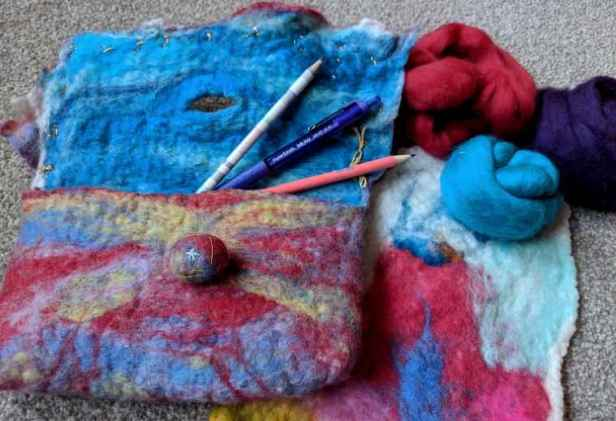 Image of wet wool felted pencil case in blues and reds with pencils in, abstract wool felted wall hanging and rolls of blue and red wool roving