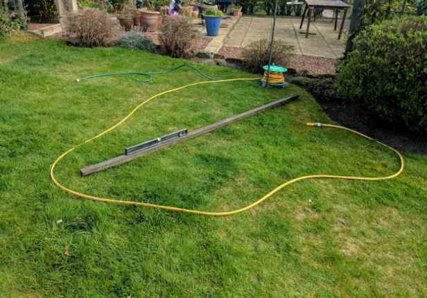 Image of grass area with yelllow hose pipe showing potential outline of pond to be dug