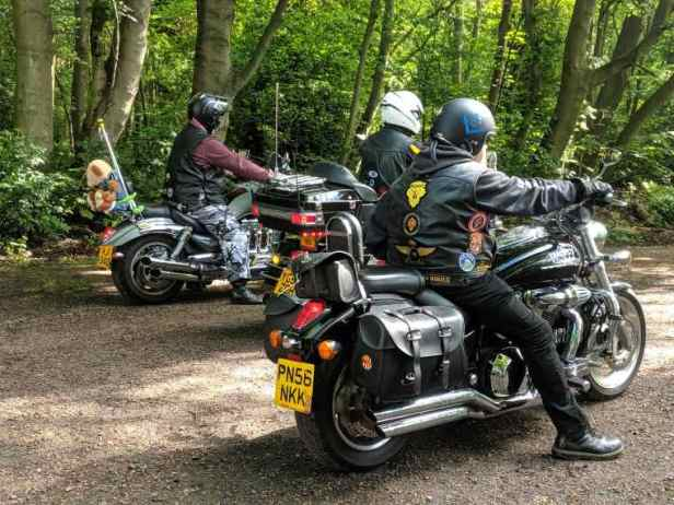 Image of 3 men on motobikes on road in woodland