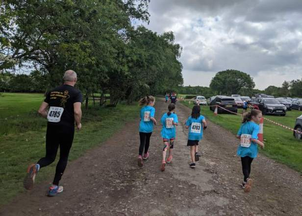 Image of 4 girls in blue T-shirts and man in black running along racetrack for Childrens Cancer Run