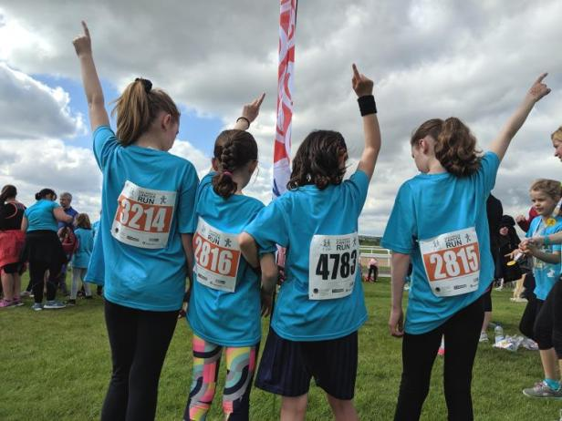 Image of 4 girls with backs to camera and hands in air wearing blue T-shirts with race numbers on back