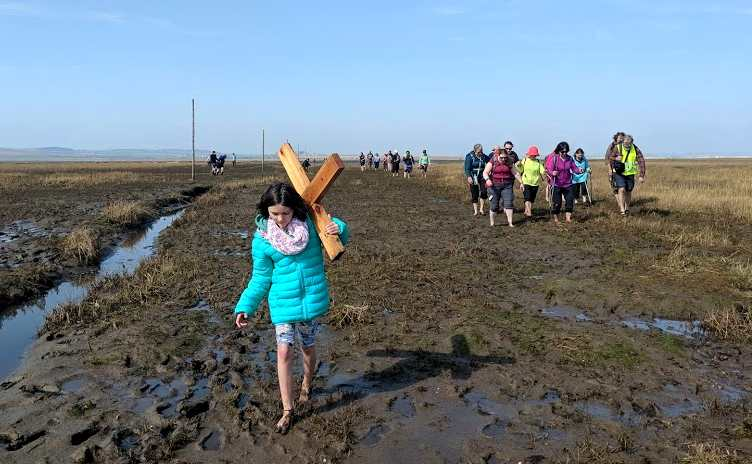 Image of girl in green coat carrying wooden cross over shoulder with barefeet in mud and group of people to right